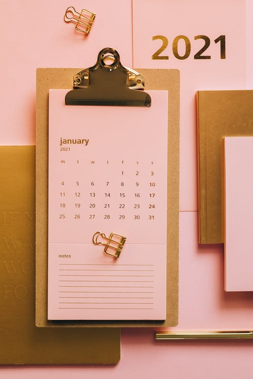 Clipboard with pink calendar on table