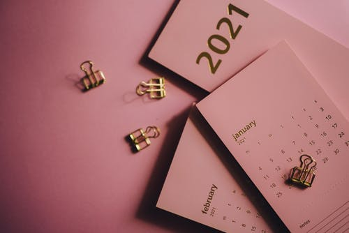 Set of contemporary calendars and clips on pink background