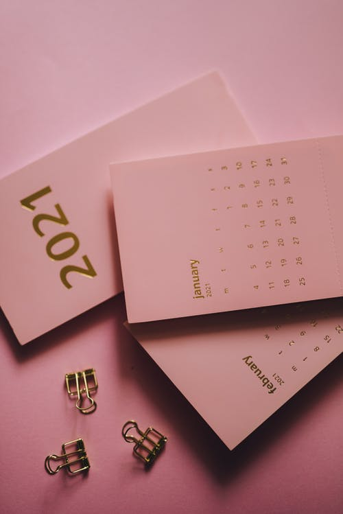 Modern calendars near metal clips on pink background