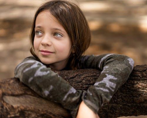 Girl in Gray Long Sleeve Shirt Lying on Brown Rock