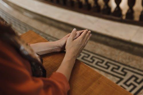 Человек в оранжевой рубашке с длинным рукавом держит за руку человека в черных штанах