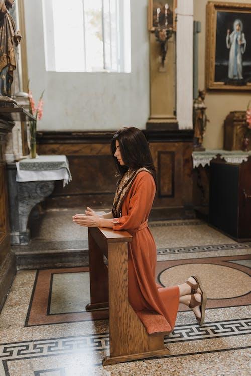 Женщина в оранжевом платье стоит на коричневом деревянном столе