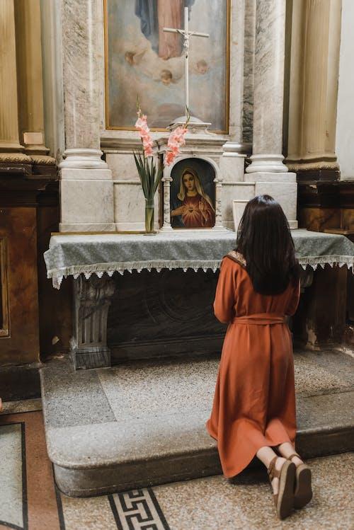 женщина в оранжевом платье стоит перед черно белым мраморным столом