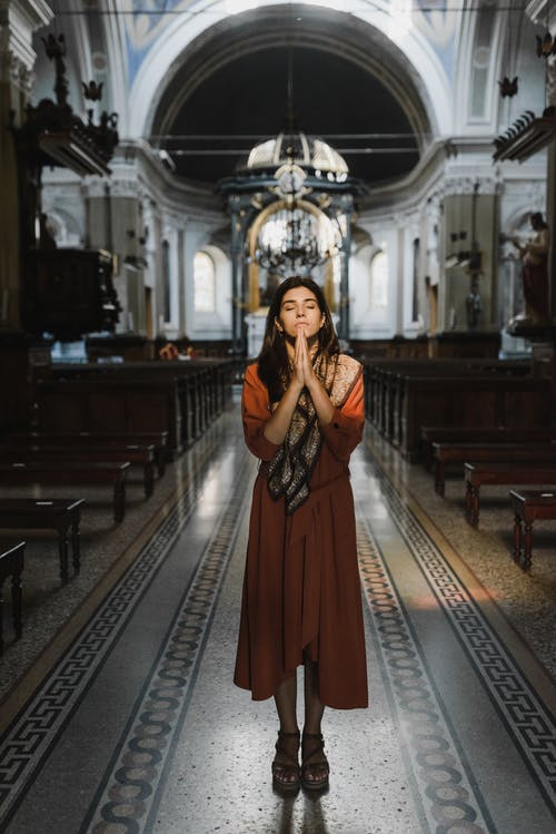 Женщина в коричневом платье стоит на коричневой деревянной лестнице
