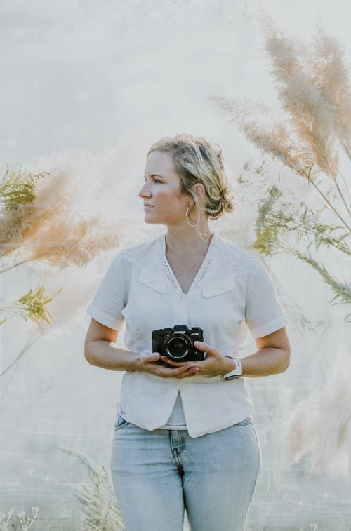 Woman in White Polo Shirt Holding Black Dslr Camera