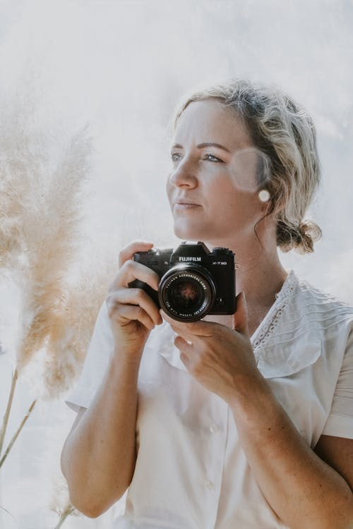 Woman in White Shirt Holding Black Dslr Camera