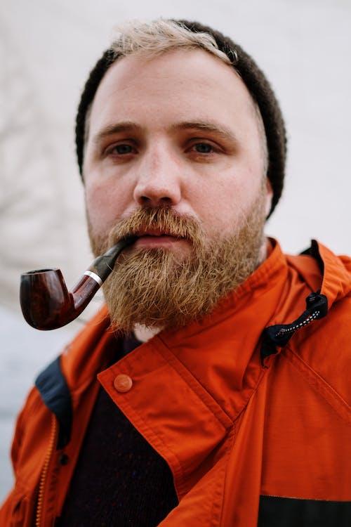 Man in Orange Jacket Smoking Cigarette
