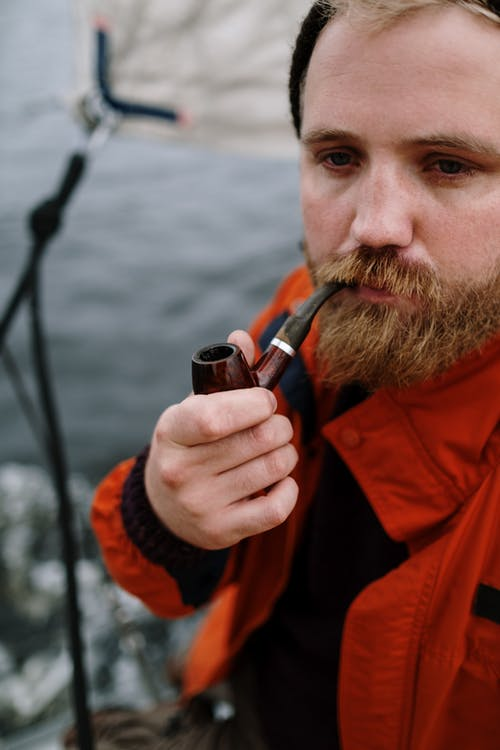 Man in Red Jacket Holding Black Box Mod