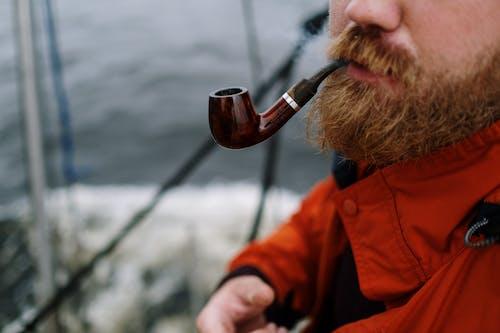 Man in Red Jacket Holding Brown Smoking Pipe