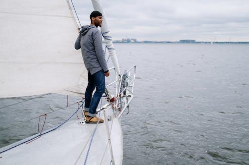 Homem De Jaqueta Cinza E Jeans Azul Em Pé No Barco Branco