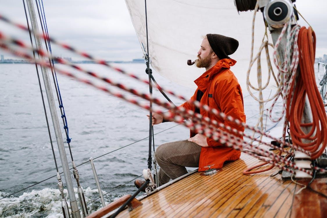 Mann In Der Orangefarbenen Jacke, Die Auf Braunem Holzboot Sitzt