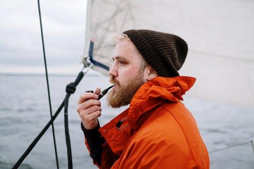 Man in Black Knit Cap and Orange Jacket Smoking Cigarette