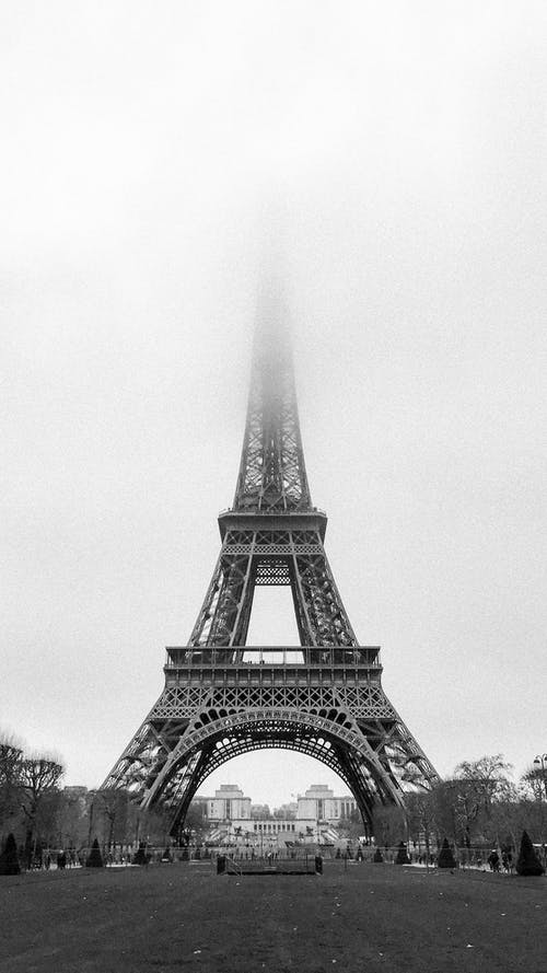 Black and white exterior of majestic famous Eiffel Tower with peak in dense fog