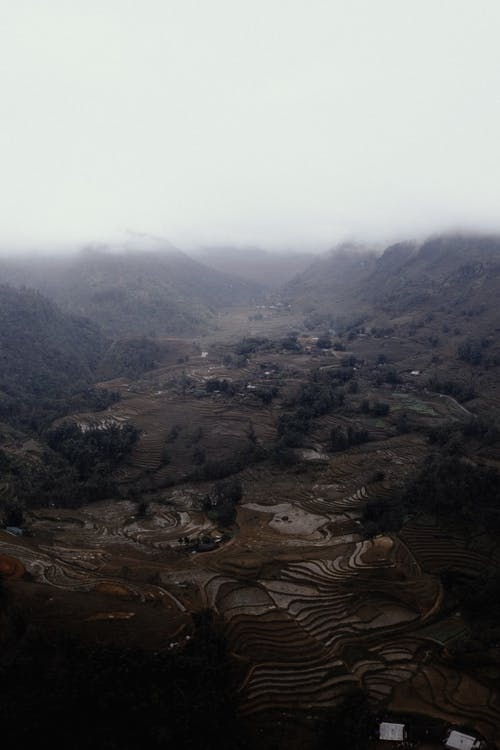 Drone view scenery of spacious green highland valley near small settlement on foggy weather