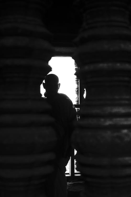 Silhouette of monk standing in old pagoda