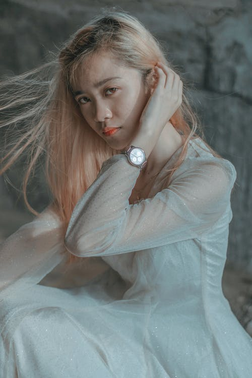Calm young Asian female with light hair in white dress touching hair and sitting against stone wall