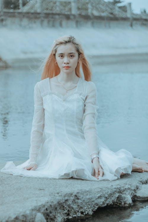 Thoughtful Asian woman in white dress sitting near water