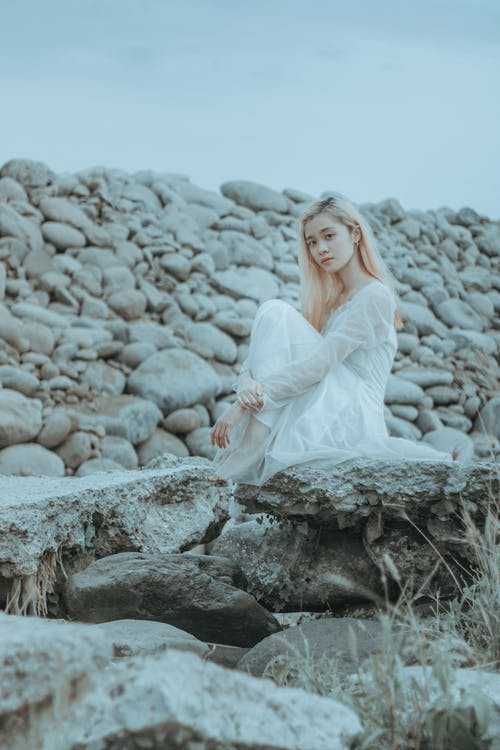 Thoughtful Asian lady in dress sitting on rocky surface