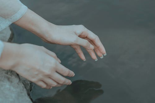 Crop anonymous female in elegant clothes reaching hands to calm water in daytime