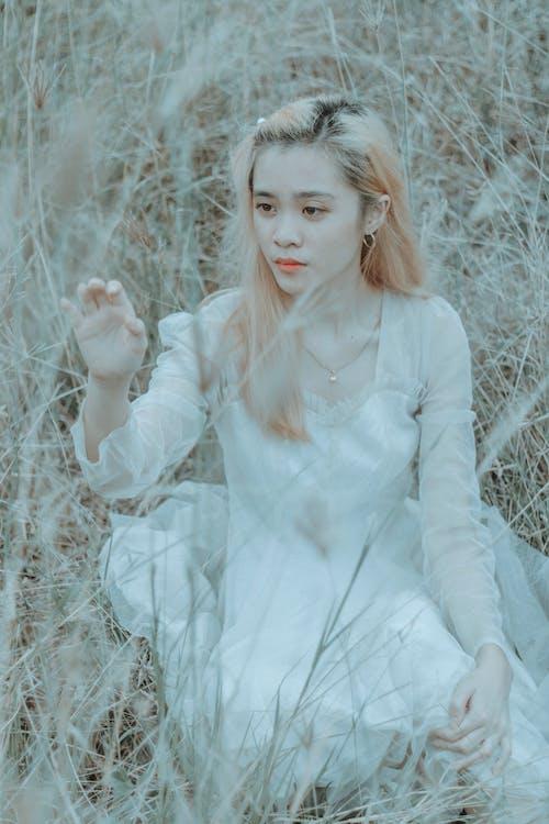 Young serious Asian woman touching grass