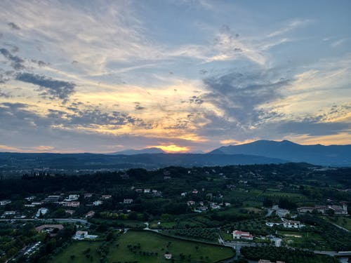 Amazing drone view of residential houses located in green valley under cloudy sunset sky in mountainous countryside