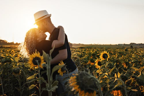 Woman in Black Tank Top and White Sun Hat Sitting on Sunflower Field