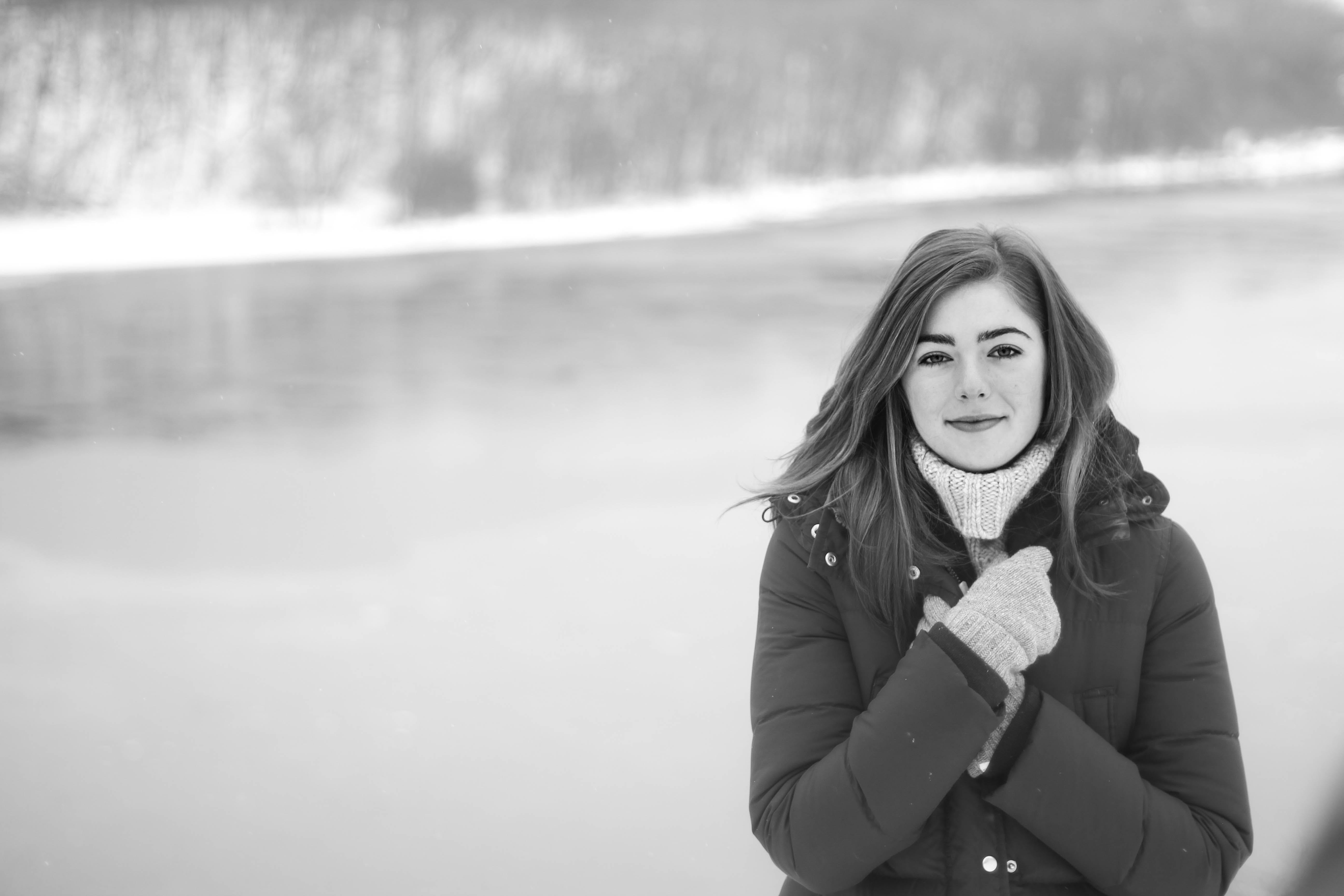 Brown Haired Woman in Black Puffer Coat Standing Near the Water