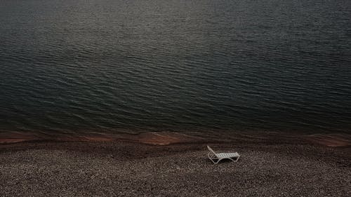 White Plastic Chair on Brown Sand Beside Body of Water