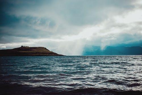 Wavy ocean with rocky island in rainy weather