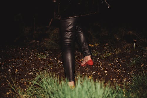 Person in Black Leather Jacket and Black Pants Standing on Green Grass Field