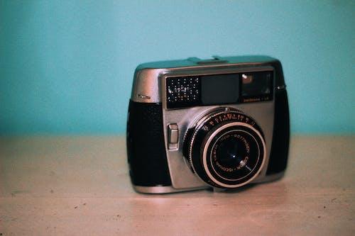 Retro photo camera on table on blue background