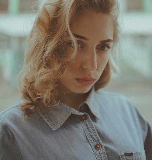 Crop sad female with curly blond hair wearing casual shirt standing on blurred street background and looking away