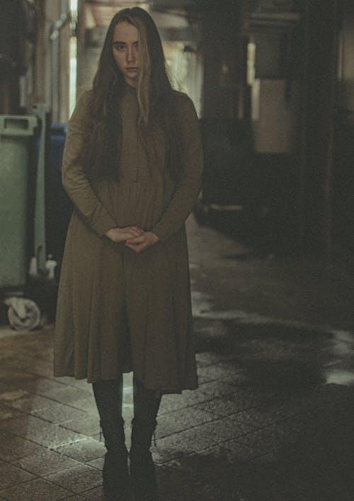Woman in Brown Coat Standing on Gray Concrete Floor