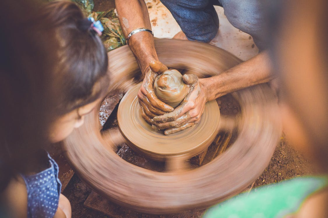 Person Making Clay Pot in Front of Girl during Daytime