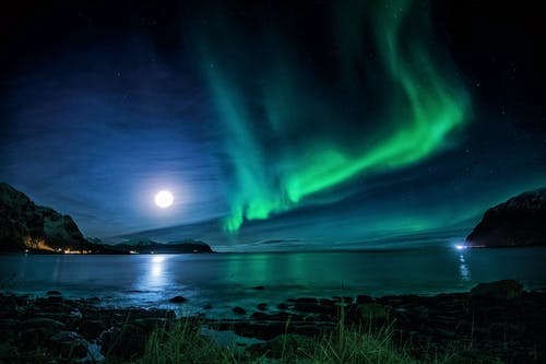 Scenic view of glowing sun with aurora in sky reflecting in sea near mountains at dusk
