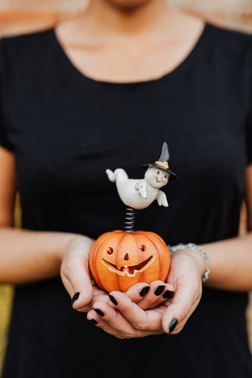 Person Holding a Toy Jack O Lantern with a Ghost