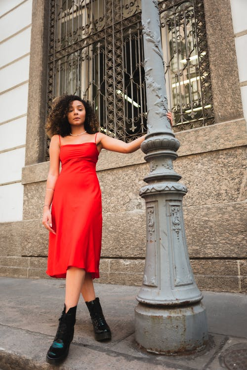 Woman in Red Tube Dress Standing Beside Gray Concrete Post