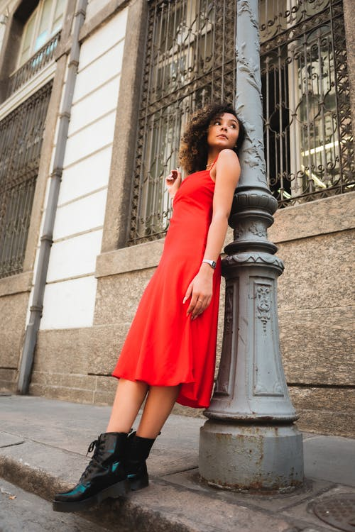 Woman in Red Dress Standing on Gray Concrete Post