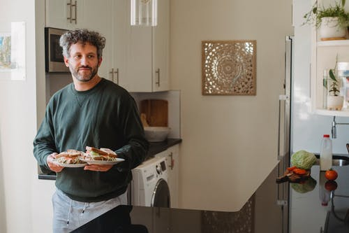 Calm man carrying plates with sandwiches