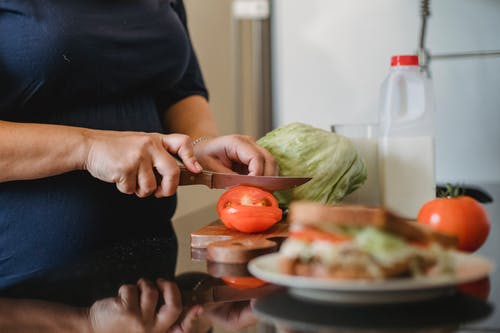 Woman cooking cutting vegetables for sandwiches