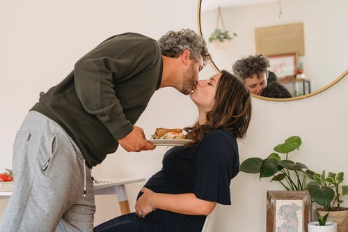 Happy couple kissing in kitchen in cozy apartment