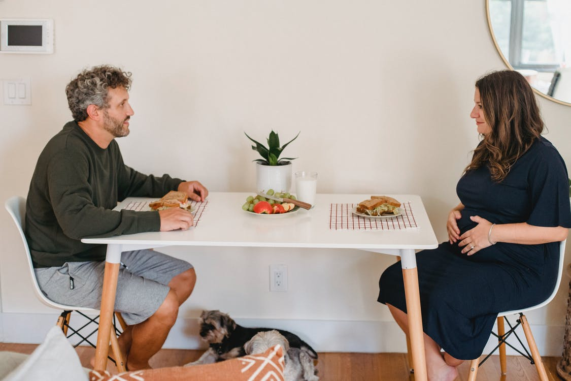Happy couple eating sandwiches at breakfast in cozy apartment