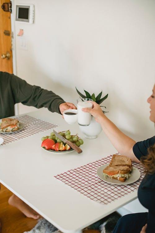 Crop couple having breakfast in kitchen