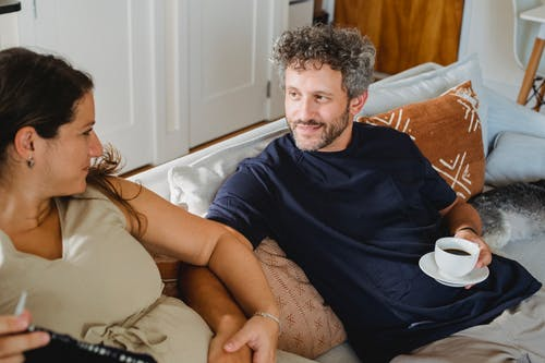 Happy man with hot drink looking at wife