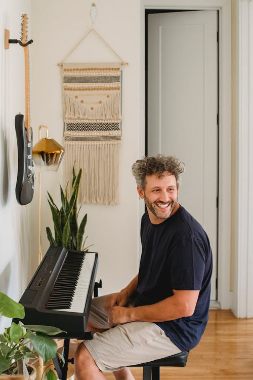 Adult cheerful bearded man with curly gray hair sitting on chair near piano and looking away