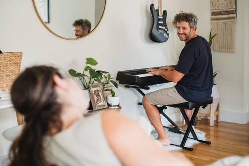 Loving adult male with beard and curly gray hair at wife while playing piano in cozy living room