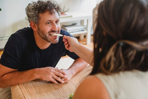 Cheerful bearded male with curly gray hair biting slice of apple from hand of wife