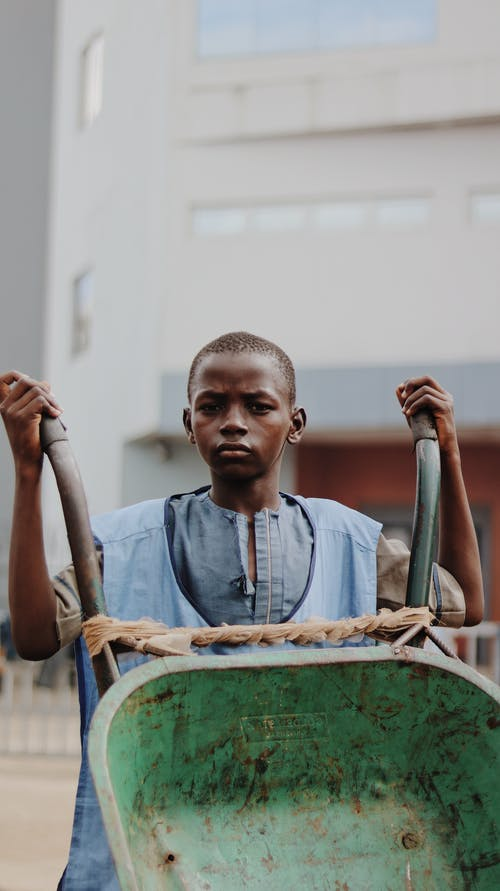 Pensive black child with wheelbarrow by modern building