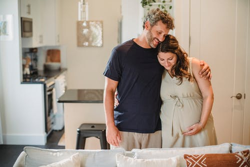 Smiling bearded man with curly gray hair embracing happy pregnant wife in beige dress in room of modern apartment