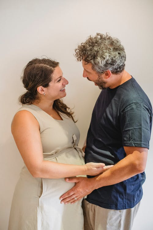 Side view of bearded man touching pregnant tummy of smiling wife in casual dress while standing and talking against white background